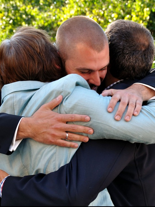 Man hugging parents